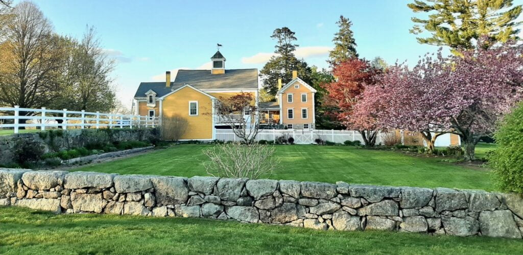 Photograph of landscape with yellow barn in the background and a stone wall in the foreground.